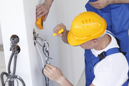 Un électricien change une prise murale
