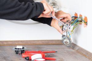 Un électricien change une prise électrique murale
